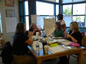 teachers sitting around table with data charts