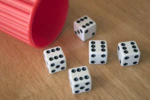cup overturned, five dice scattered on a table each showing six dots