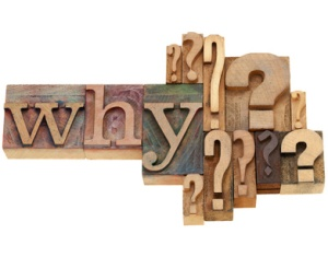 the word why and many question marks on wooden type-face blocks
