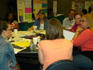 teachers sitting around table discussing professional insights about data