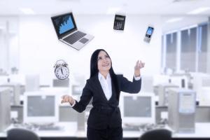 woman in computer lab juggling laptop, tabley, clock, smartphone