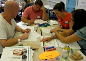 Four teachers at a table analyzing data with resources on the table