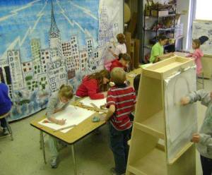 group of students work an selective parts of a mural of a cityscape